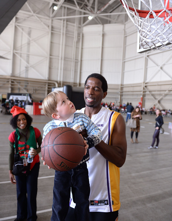 . Ex-Laker A.C. Green helps Matthew Babcock reach the rim. Holiday in the Hangar at Delta Airlines at LAX. About 100 children from Children\'s Hospital, LA got to ride on a plane to the North Pole where holiday games and fun plus Santa awaited. (Dec 11, 2013. Photo by Brad Graverson/The Daily Breeze)