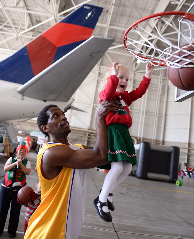 . Ex-Laker A.C. Green helps Eliza Babcock make a basket. Holiday in the Hangar at Delta Airlines at LAX. About 100 children from Children\'s Hospital, LA got to ride on a plane to the North Pole where holiday games and fun plus Santa awaited. (Dec 11, 2013. Photo by Brad Graverson/The Daily Breeze)