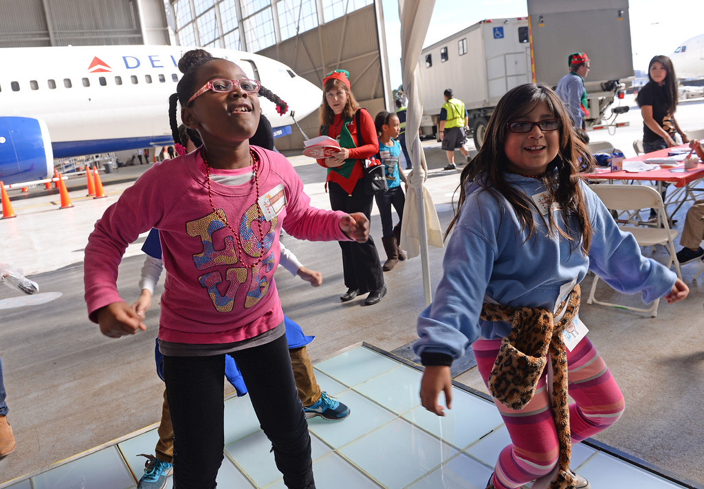 . Dancing to holiday tunes. Holiday in the Hangar at Delta Airlines at LAX. About 100 children from Children\'s Hospital, LA got to ride on a plane to the North Pole where holiday games and fun plus Santa awaited. (Dec 11, 2013. Photo by Brad Graverson/The Daily Breeze)