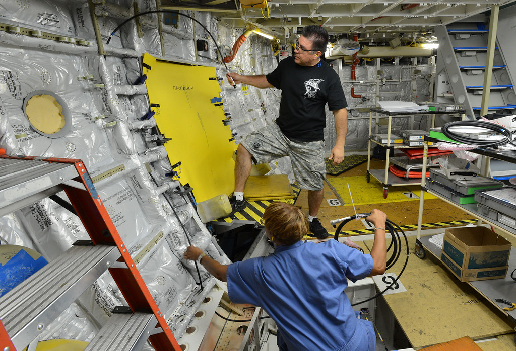 . Long Beach, Calif., -- 08-13-13-   Electricians Pete Gonzalez and Dianne Maye work on a new Boeing C-17 Globemaster III as it\'s assembled at the C-17 plant in Long Beach Calif.    Stephen Carr/  Los Angeles Newspaper Group