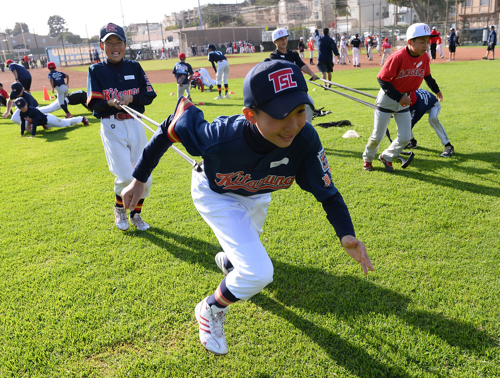 . Japanese little leaguers Rui Yamaguchi, front, runs as Kensuke Aoyagi holds on with a stretch band during pre-game practiceWednesday. A tournament will be held in El Segundo this weekend at Brett Field. Photo by Brad Graverson/The Daily Breeze 3-27-14