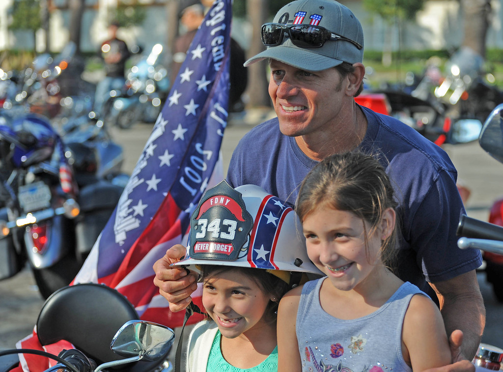 . Long Beach fire fighters rode their motorcycles from Cooks Corner in Orange County to Long Beach Wednesday in remembrance of 9-11. More than two hundred riders participated.  Gracie, 7, and Ruby, 9, Milburn, from Buena Park, whose father is a Long Beach fire fighter, pose for a photo with Gary Biggerstaff. Wednesday, September 11, 2013,  Long Beach, CA. Photo by Steve McCrank / Daily Breeze