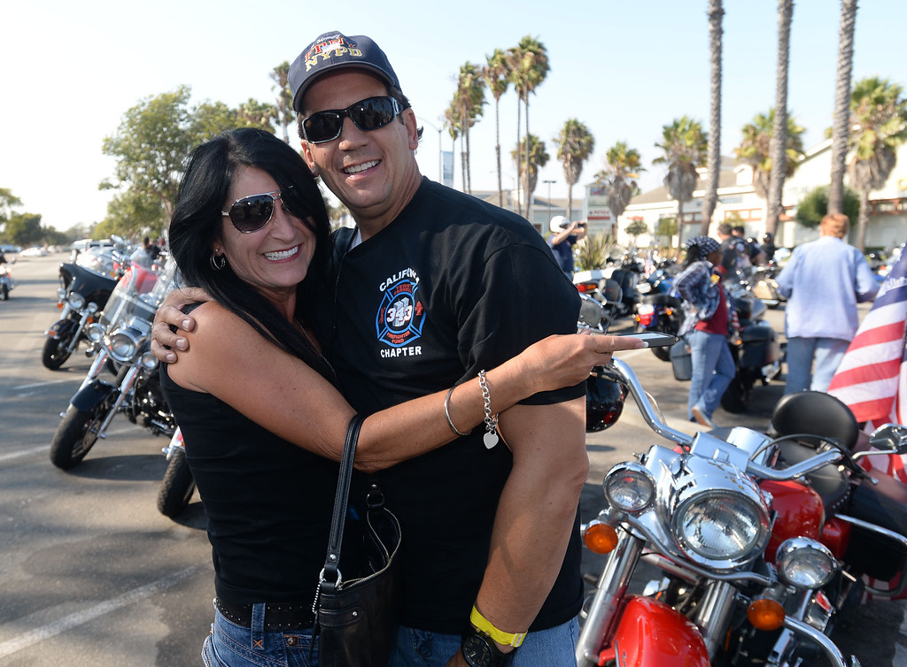 . Long Beach fire fighters rode their motorcycles from Cooks Corner in Orange County to Long Beach Wednesday in remembrance of 9-11. More than two hundred riders participated.  Judy Mark poses for a photo with Long Beach (and former New York) fire fighter Rich Brandt. Wednesday, September 11, 2013,  Long Beach, CA. Photo by Steve McCrank / Daily Breeze