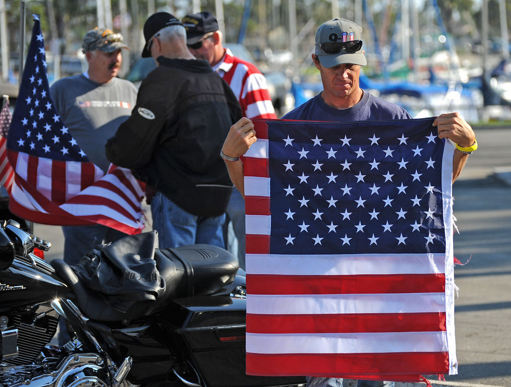 . Long Beach fire fighters rode their motorcycles from Cooks Corner in Orange County to Long Beach Wednesday in remembrance of 9-11. More than two hundred riders participated.  Gary Biggerstaff folds an American flag that was flown on back of one of the motorcycles. Wednesday, September 11, 2013,  Long Beach, CA. Photo by Steve McCrank / Daily Breeze