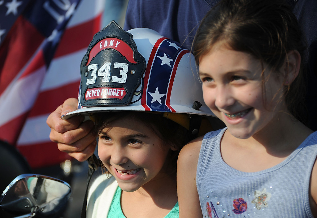 . Long Beach fire fighters rode their motorcycles from Cooks Corner in Orange County to Long Beach Wednesday in remembrance of 9-11. More than two hundred riders participated.  Gracie, 7, and Ruby, 9, Milburn, from Buena Park, whose father is a Long Beach fire fighter, pose for a photo with Gary Biggerstaff\'s helmet. Wednesday, September 11, 2013,  Long Beach, CA. Photo by Steve McCrank / Daily Breeze