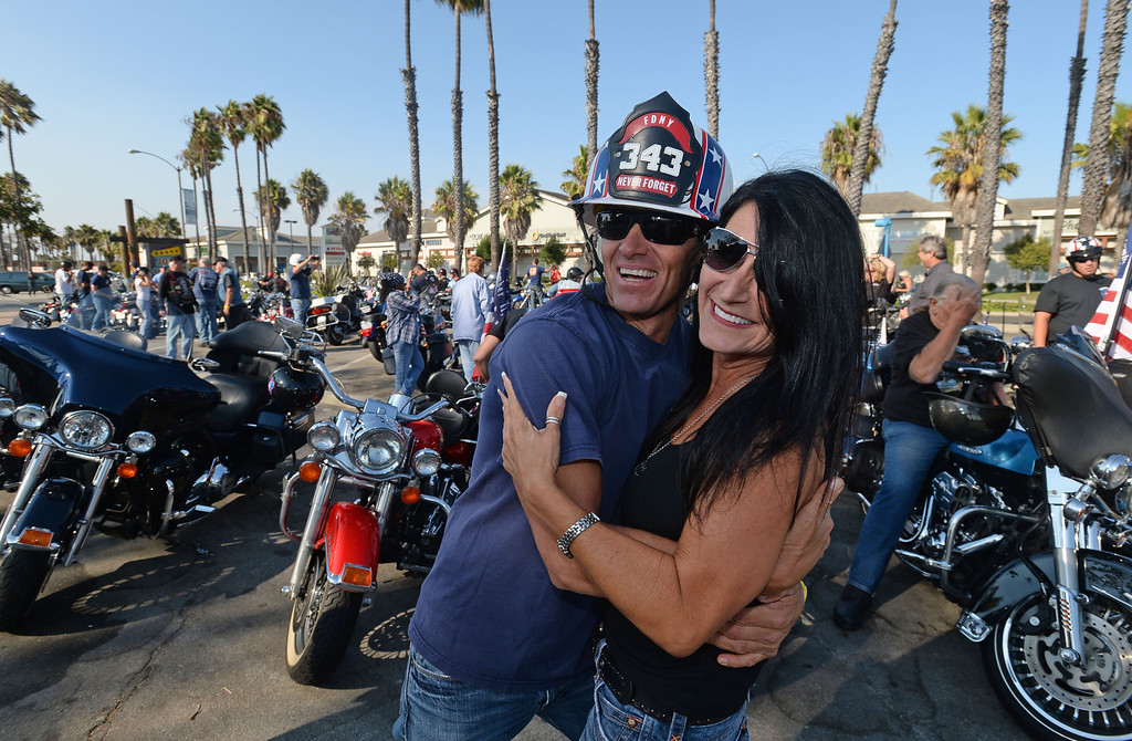 . Long Beach fire fighters rode their motorcycles from Cooks Corner in Orange County to Long Beach Wednesday in remembrance of 9-11. More than two hundred riders participated.  Gary Biggerstaff, a Long Beach fire engineer, gives Judy Mark a hug at the end of the ride while still wearing his fire-motorcycle helmet with the number 343 which represents the fire fighters killed in 9-11. Wednesday, September 11, 2013,  Long Beach, CA. Photo by Steve McCrank / Daily Breeze