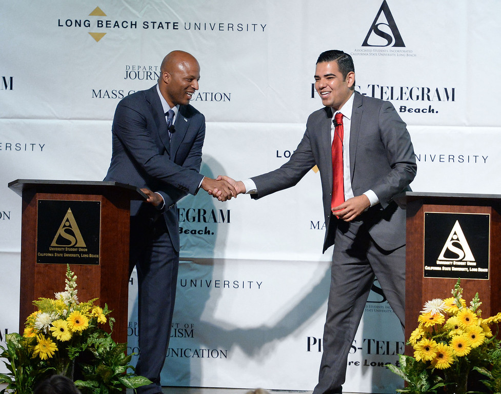 . Real estate investor Damon Dunn, left, and Vice Mayor Robert Garcia, right, shake hands after a funny moment when the topic of negative campaigns came up, in the debate at Cal State University Long Beach in Long Beach, CA. on Tuesday May 14, 2014. (Photo by Sean Hiller/ Daily Breeze).