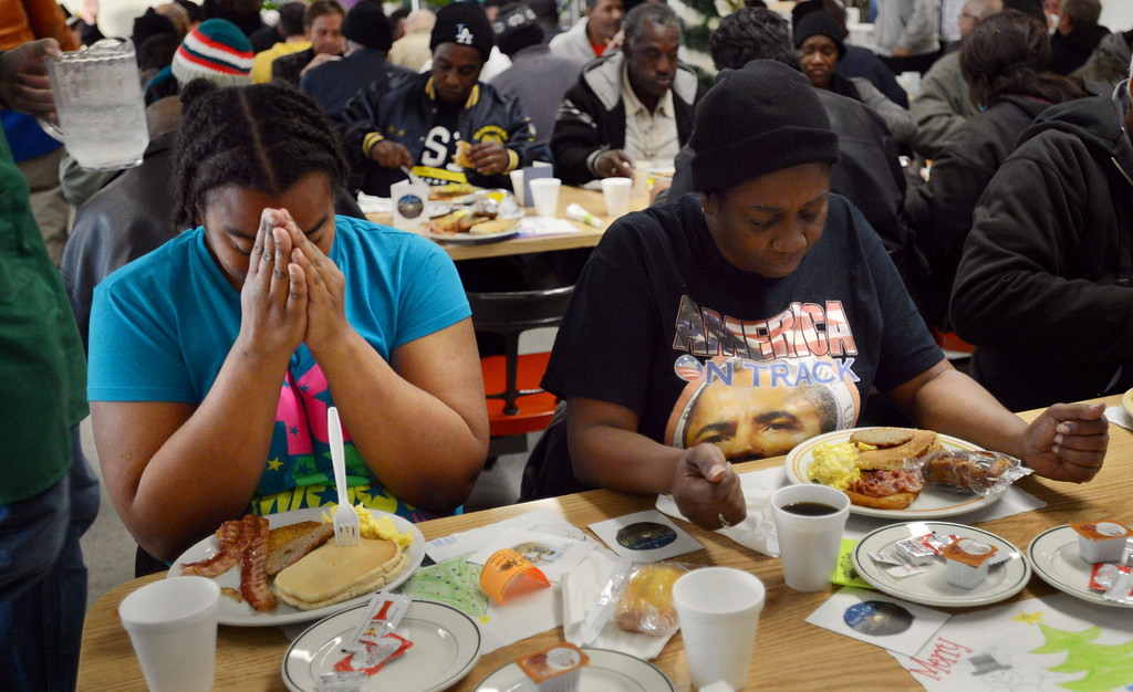 . Christine Wimberly,left, and her mother Jennifer Simon Jobity say a prayer before eating, as the Long Beach Rescue Mission hosted a Christmas Breakfast Tuesday morning from 7 AM to 10 AM. Between 500 and 600 meals were served.   Long Beach, Calif. Tuesday, December 24, 2013.   (Photo by Stephen Carr / Daily Breeze)
