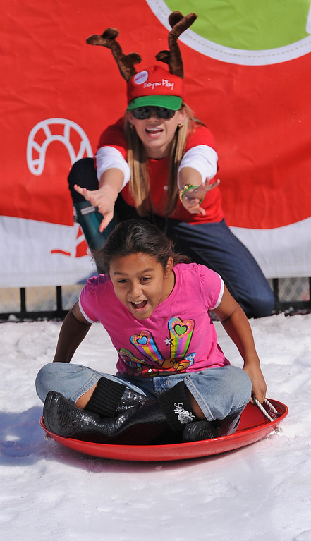 . Jade Joya screams as she slides down a hill of snow. Mattel Corp. brought lots of snow and fun games to Washington Elementary in Hawthorne for its 12 Days of Play event.  (Dec 12, 2013. Photo by Brad Graverson/The Daily Breeze)