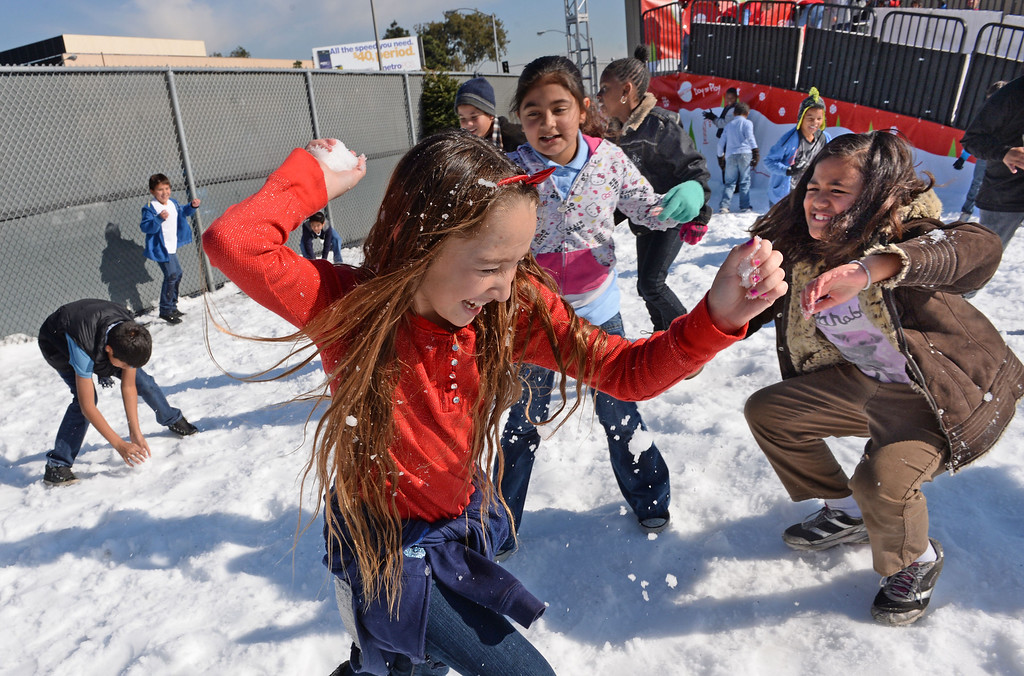 . Anahi Veronica (cq) in red, center, dodges a few snowballs from her friends. Mattel Corp. brought lots of snow and fun games to Washington Elementary in Hawthorne for its 12 Days of Play event.  (Dec 12, 2013. Photo by Brad Graverson/The Daily Breeze)