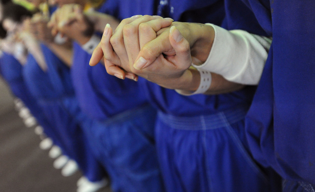 . Inmates hold hands in prayer in the presence of Our Lady of Guadalupe\'s portrait at morning Mass for incarcerated women at the Los Angeles County Century Regional Detention Facility in Lynwood on Sunday, Nov. 17, 2013. (Photo by Sean Hiller/Long Beach Press Telegram)
