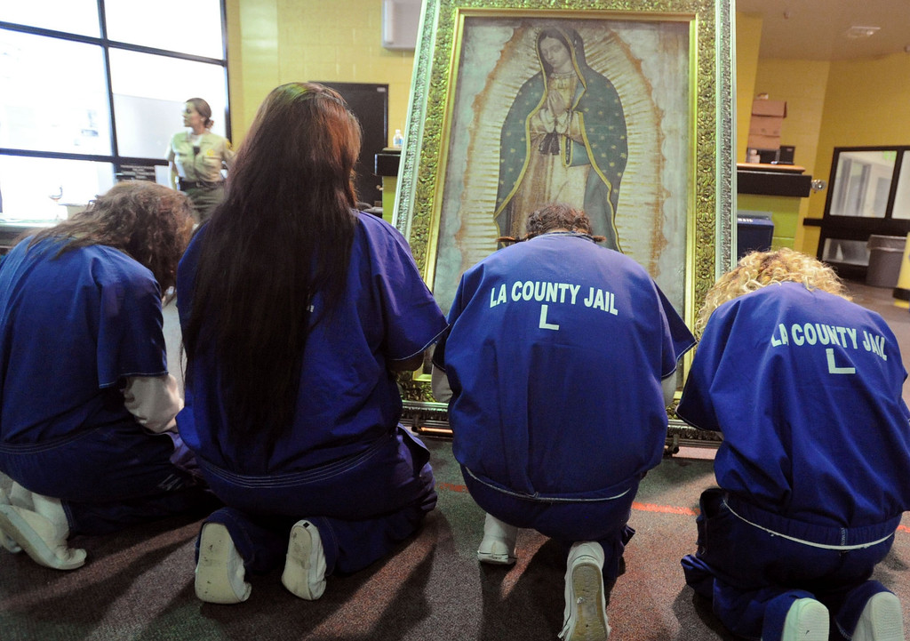 . Inmates kneel in prayer in the presence of Our Lady of Guadalupe\'s portrait at morning Mass for incarcerated women at the Los Angeles County Century Regional Detention Facility in Lynwood on Sunday, Nov. 17, 2013. (Photo by Sean Hiller/Long Beach Press Telegram)