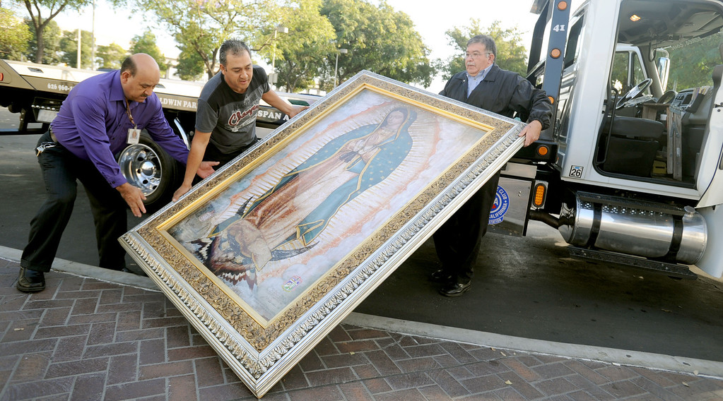 . Teodoro Rodriguez, left, Bernardo Barajas, center, and Antonio Garcia unload the image of Our Lady of Guadalupe for morning Mass for incarcerated women at the Los Angeles County Century Regional Detention Facility in Lynwood on Sunday, Nov. 17, 2013. (Photo by Sean Hiller/Long Beach Press Telegram).