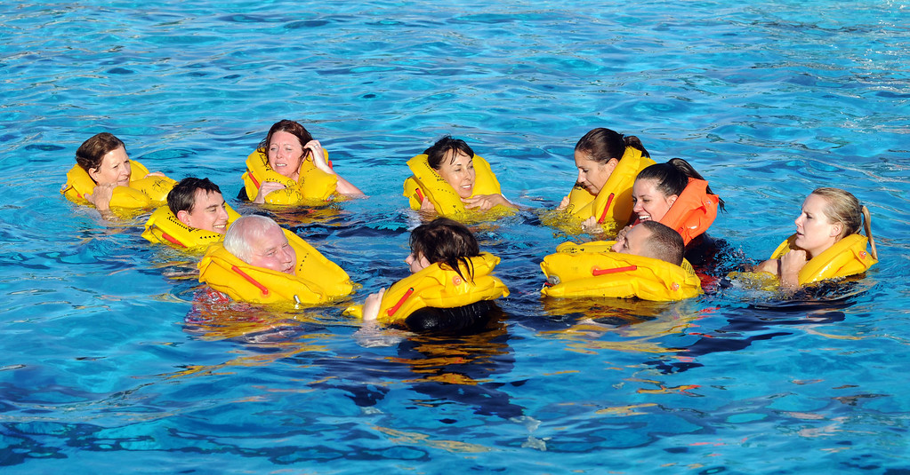 . Long Beach, Calif., -- 09-26-13- Aircare students train in the water next to an emergency raft, at the LBSU pool.   Aircare Solutions Group is comprised of business aviation products and services that combined, provide crew member emergency procedures training, tele-medical assistance, and crew staffing to flight departments worldwide.    Stephen Carr/  Daily Breeze