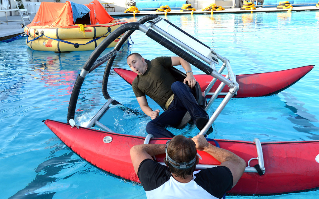 . Long Beach, Calif., -- 09-26-13- Aircare West Coast Training Center co-manager and instructor Frank Hayes assists student Adam McCain as he is dunked in simulating an underwater plane crash, in a during training at the LBSU pool.   Aircare Solutions Group is comprised of business aviation products and services that combined, provide crew member emergency procedures training, tele-medical assistance, and crew staffing to flight departments worldwide.    Stephen Carr/  Daily Breeze