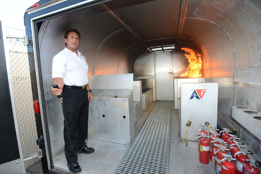 . Long Beach, Calif., -- 09-26-13- Aircare West Coast Training Center Co-manager and instructor Frank Hayes demonstrates a simulated fire inside a cabin fire simulator, at an Aircare Solutions Group open house,  for its New Training Facility in Long Beach. Aircare Solutions Group is comprised of business aviation products and services that combined, provide crew member emergency procedures training, tele-medical assistance, and crew staffing to flight departments worldwide.    Stephen Carr/  Daily Breeze
