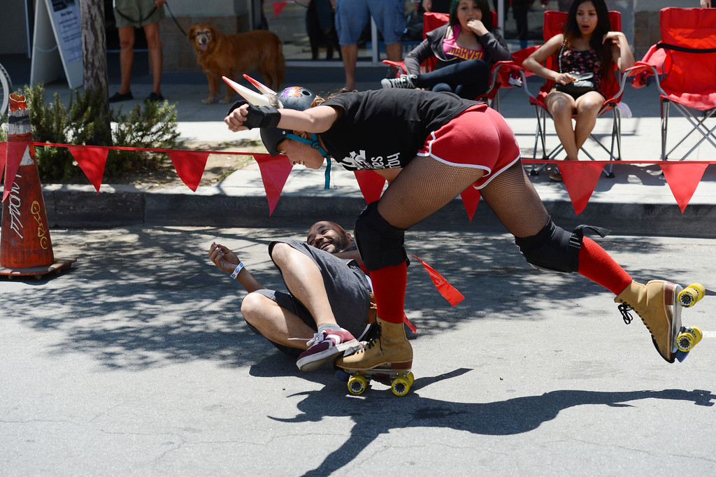 """. Press -Telegram reporter Richard Guzman,left, is rundown by  Beach Cities Roller Derby\'s Ashley  \"""" Bambi \""""  Smith in the first Running of the Dames,  along Pine Avenue between and 8th Streets. Fashioned after the Running of the Bulls, local derby girls chase down runners along a course, grabbing two red flags off the waist of the runner. Last runner standing wins the race.  Long Beach Calif., Saturday May 31,  2014.     (Photo by Stephen Carr / Daily Breeze)"""