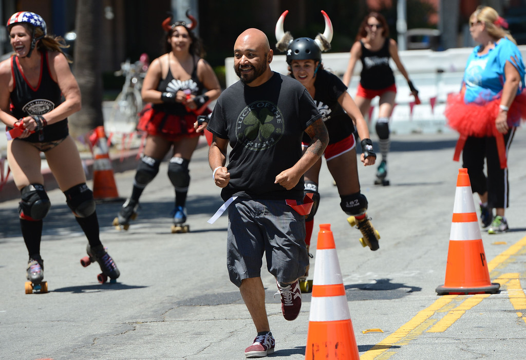. Press -Telegram reporter Richard Guzman run in the first Running of the Dames along Pine Avenue between and 8th Streets. Fashioned after the Running of the Bulls, local derby girls chase down runners along a course, grabbing two red flags off the waist of the runner. Last runner standing wins the race.  Long Beach Calif., Saturday May 31,  2014.     (Photo by Stephen Carr / Daily Breeze)