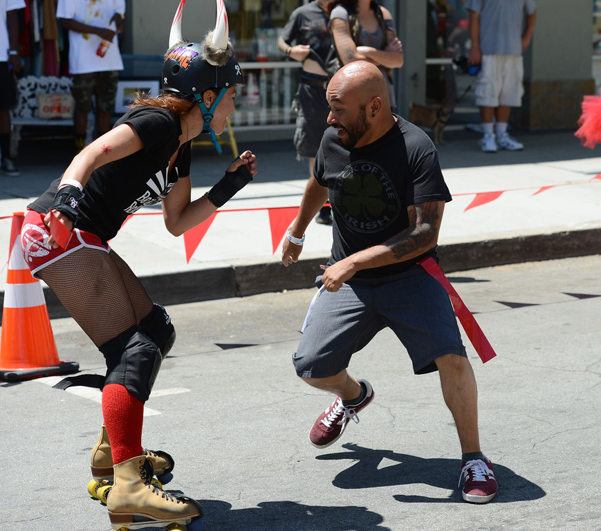 """. Press -Telegram reporter Richard Guzman,right, is rundown by  Beach Cities Roller Derby\'s Ashley  \"""" Bambi \""""  Smith in the first Running of the Dames along Pine Avenue between and 8th Streets. Fashioned after the Running of the Bulls, local derby girls chase down runners along a course, grabbing two red flags off the waist of the runner. Last runner standing wins the race.  Long Beach Calif., Saturday May 31,  2014.     (Photo by Stephen Carr / Daily Breeze)"""