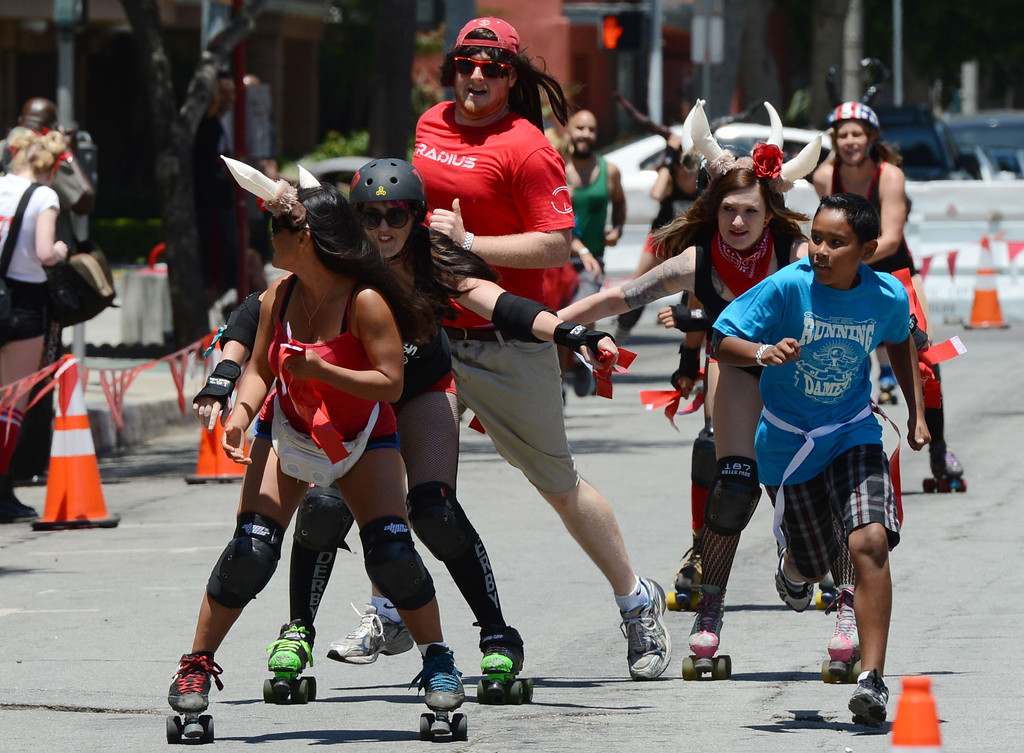 . The first Running of the Dames,  along Pine Avenue between and 8th Streets. Fashioned after the Running of the Bulls, local derby girls chase down runners along a course, grabbing two red flags off the waist of the runner. Last runner standing wins the race.  Long Beach Calif., Saturday May 31,  2014.     (Photo by Stephen Carr / Daily Breeze)