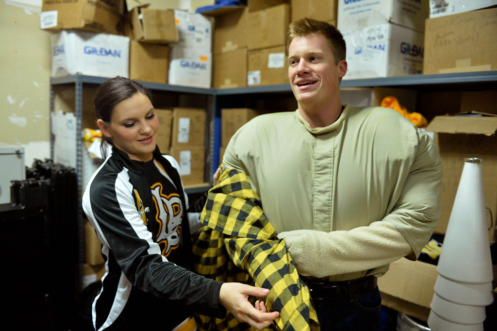 . Connor King, who is the man under the Prospector Pete mascot costume, gets help getting from girlfriend Amber Frank, captain of the cheer team, before a Long Beach State men\'s basketball game at Walter Pyramid in Long Beach, CA. on Thursday, January 9, 2014. (Photo by Sean Hiller/ Daily Breeze).