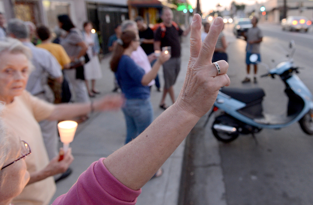 . A protester shows a piece sign to passerbyers as a group holds a candle light vigil to protest proposed bombing of Syria in Long Beach Monday September 9, 2013. (Photo by Thomas R. Cordova/ Daily Breeze)
