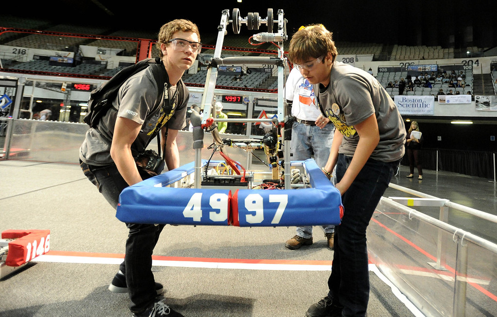 . Matthew Bilodeau, left, and Everardo Gonzalez carry the Long Beach Poly team\'s robot to the course at the First Robotics Competition, a Raytheon sponsored event where local high school students  built robots to compete, kicked off today at the Long Beach Arena in Long Beach, CA. on Wednesday March 19, 2014. (Photo by Sean Hiller/ Daily Breeze).
