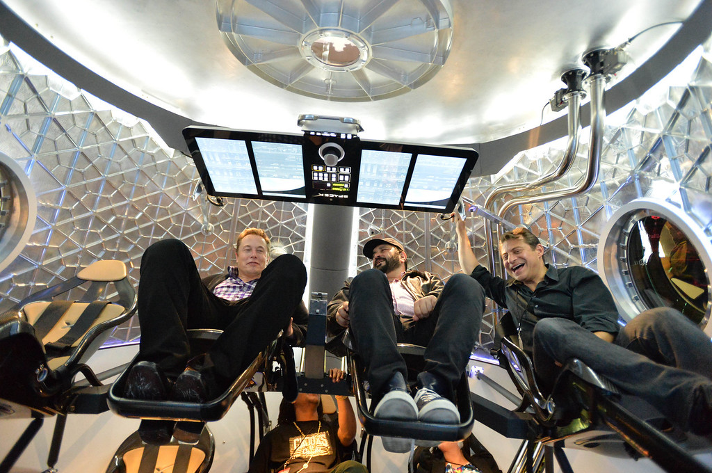 . Elon Musk, SpaceX CEO and founder, left, and VIP guests hang out inside the Dragon V2 spacecraft,  at the unveiling in Hawthorne, CA. on Thursday May 29, 2014. (Photo by Sean Hiller/ Daily Breeze).