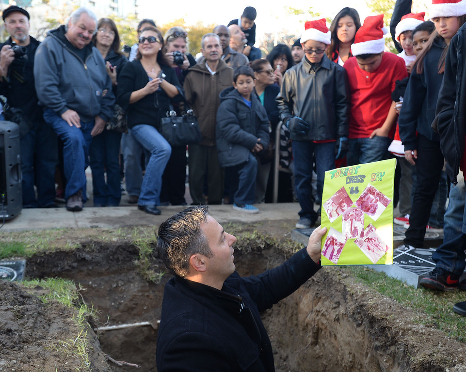 . Los Angeles City Councilman Joe Buscaino removes items from a 25 year old time capsule that was uncovered during the annual tree lighting at Pepper Tree Plaza Thursday, December 05, 2013, in San Pedro, CA.  Photo by Steve McCrank/DailyBreeze