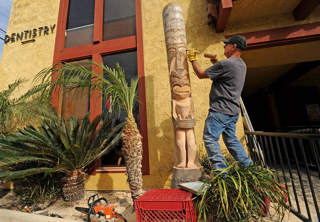 . David Shultz, a.k.a. Tiki Dave, carves a tiki out of a palm tree outside the Art House in Long Beach, CA. on Sunday, February 16, 2014. (Photo by Sean Hiller/ Daily Breeze).