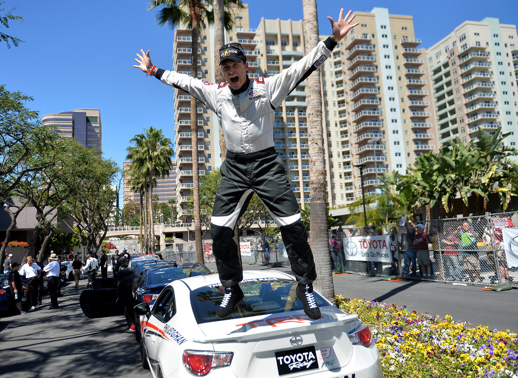 . Phil Keoghan goofs around and jumps off his car before the Friday qualifying session at the Toyota Grand Prix of Long Beach Pro/Celeb Race. Long Beach April 11, 2014.(Photo by Brittany Murray / Daily Breeze)