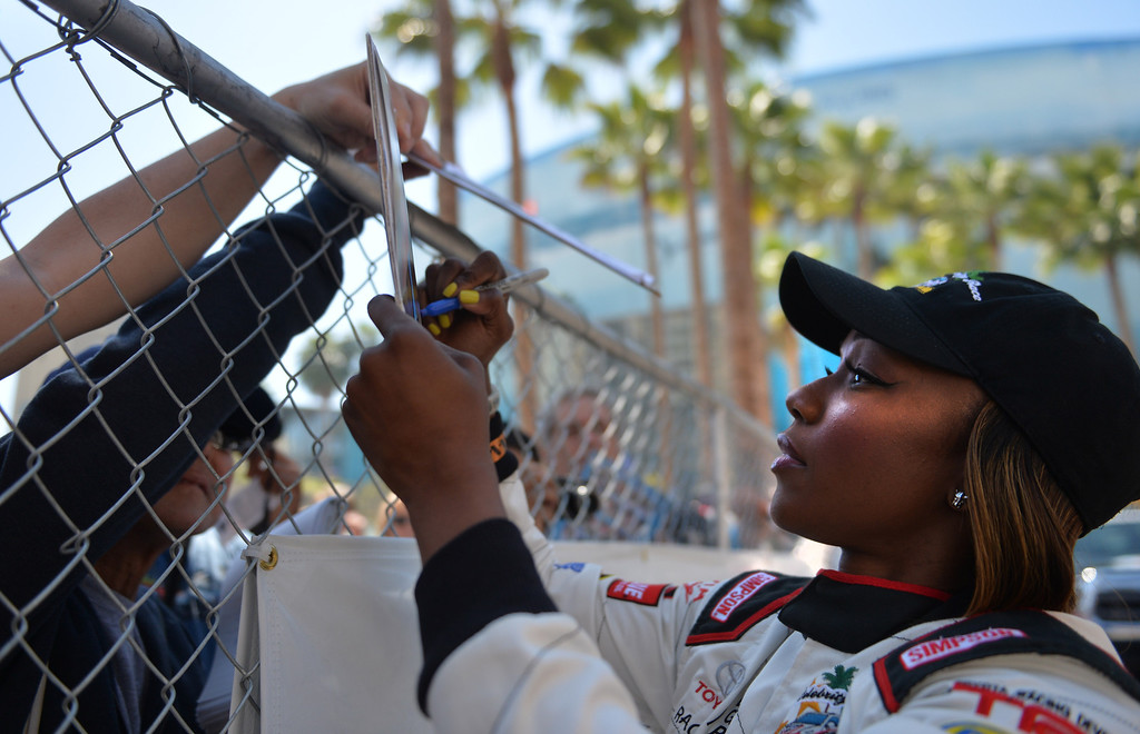 . Carmelita Jeter signs autographs for fans before a practice session at the Toyota Grand Prix of Long Beach Pro/Celeb Race. Long Beach April 11, 2014.  (Photo by Brittany Murray / Daily Breeze)