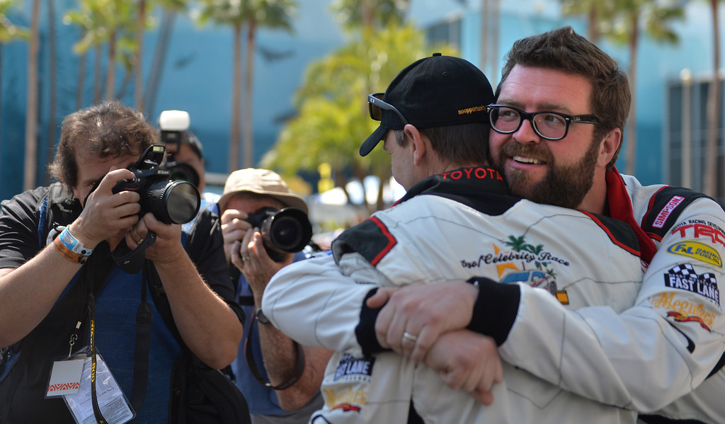 . Rutledge Wood hugs Phil Keoghan before a practice session at the Toyota Grand Prix of Long Beach Pro/Celeb Race. Long Beach April 11, 2014.  (Photo by Brittany Murray / Daily Breeze)