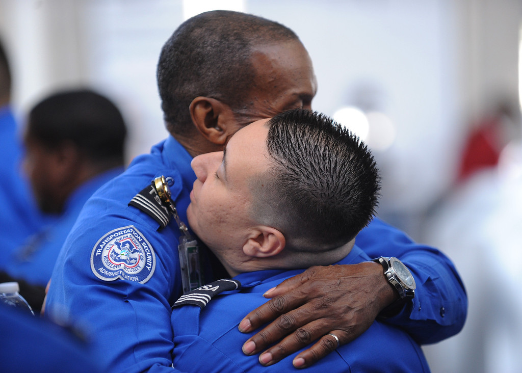 . TSA personnel comform each other before the U.S. Honor Flag arrives at Los Angeles International Airport in memory of TSA agent Gerardo Hernandez. It will be used at his upcoming funeral services. (Wed, Nov 6, 2013. Photo by Brad Graverson/The Daily Breeze/POOL)