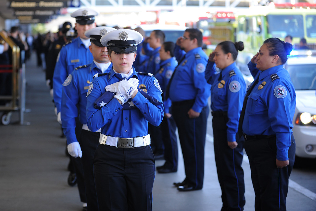 . TSA honor guard Brandy Richards carries the U.S. Honor Flag as it arrives at Los Angeles International Airport in memory of TSA agent Gerardo Hernandez. It will be used at his upcoming funeral services. (Wed, Nov 6, 2013. Photo by Brad Graverson/The Daily Breeze/POOL)
