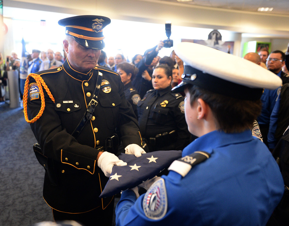 . LAX Airport Police officer Tom Dye passes the U.S. Honor Flag to TSA honor guard Brandy Richards as it arrives at Los Angeles International Airport in memory of TSA agent Gerardo Hernandez. It will be used at his upcoming funeral services. (Wed, Nov 6, 2013. Photo by Brad Graverson/The Daily Breeze/POOL)