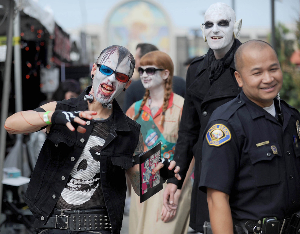 . Anthony Mejia, left, and wife Amy walk with friend Nick Danger along the Promenade as the undead invaded downtown during the annual Long Beach Zombie Walk in Long Beach, CA. on Saturday, October 26, 2013. (Photo by Sean Hiller/Press Telegram).