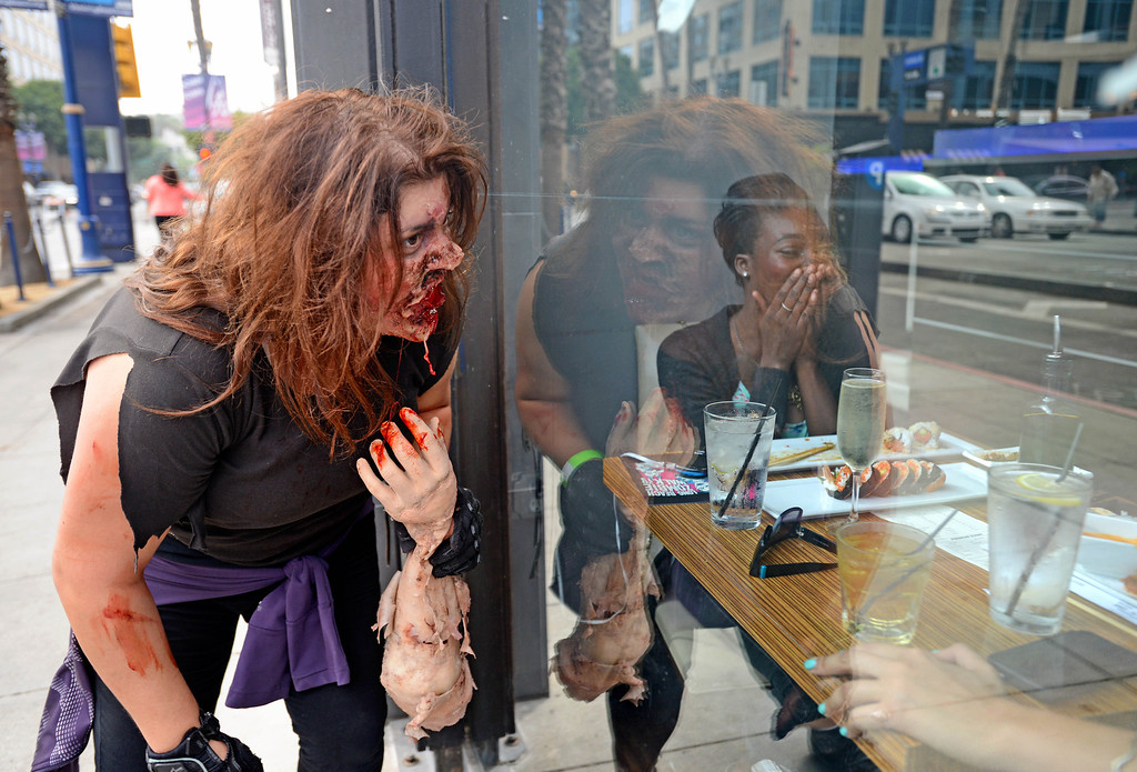 . Zombie Jennifer Maimone, a special effects makeup artist with UnmaskedFX, scares Jade Study, while eating lunch at Octopus Japanese Restaurant as the undead invaded downtown during the annual Long Beach Zombie Walk in Long Beach, CA. on Saturday, October 26, 2013. (Photo by Sean Hiller/Press Telegram).
