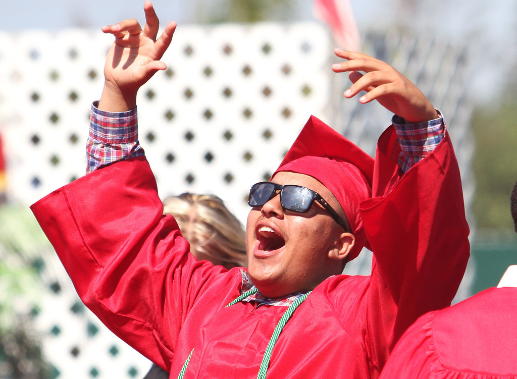 . Rodney Cunningham raises his arms into the air in celebration during Lakewood High School\'s commencement Thursday at Veterans Memorial Stadium in Long Beach, CA Thursday, June 12, 2014. (Photo by Mark Dustin for the Press-Telegram)