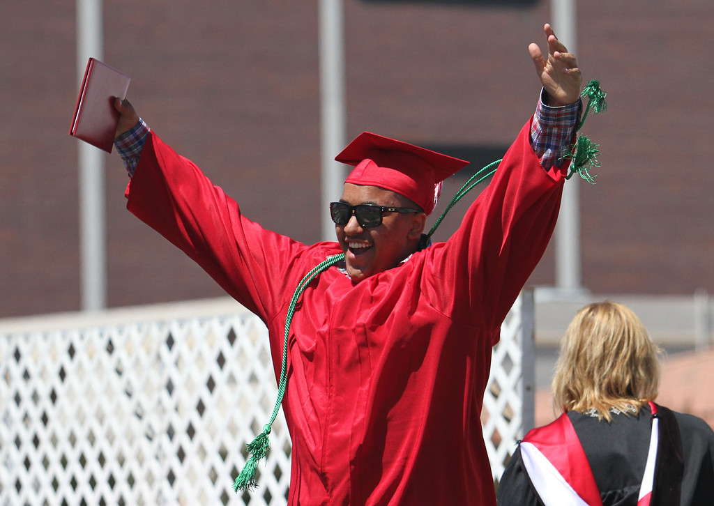 . Rodney Cunningham raises his arms into the air after getting his diploma holder during Lakewood High School\'s commencement Thursday at Veterans Memorial Stadium in Long Beach, CA Thursday, June 12, 2014. (Photo by Mark Dustin for the Press-Telegram)
