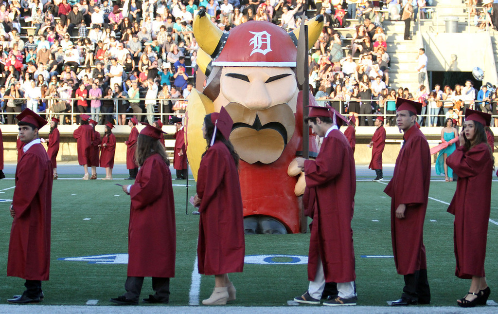 . Graduate candidates waiting in line during the Diploma Presentation pass by a Viking statue on the field during Downey High School\'s 111th Commencement Ceremony Wednesday evening in Falcon Stadium at Cerritos College in Norwalk, CA Wednesday, June 18, 2014. (Photo by Mark Dustin for the Press-Telegram)