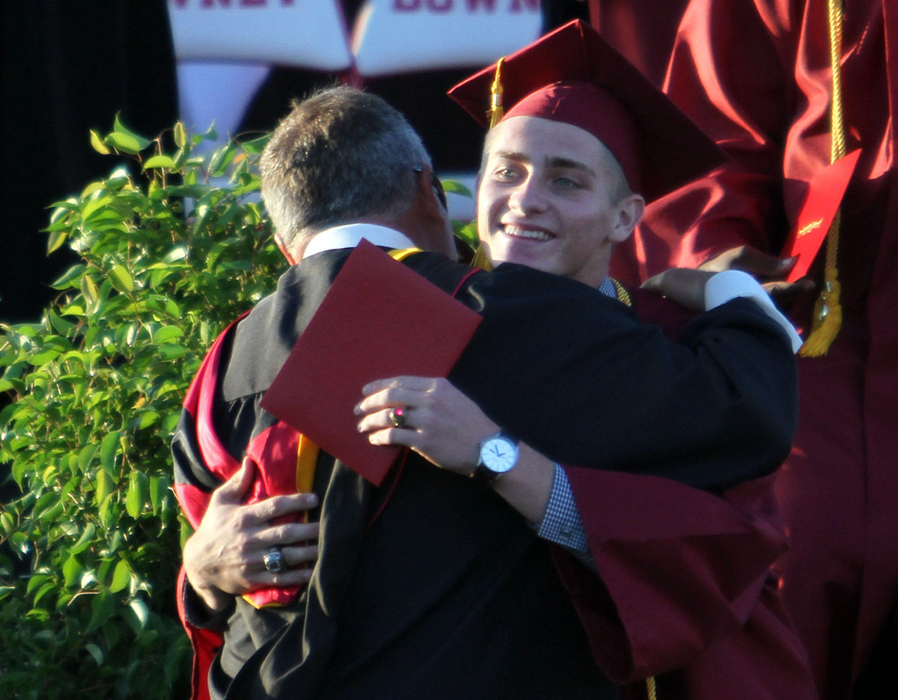 . Principal Tom Houts, left, hugs a graduate candidate during Downey High School\'s 111th Commencement Ceremony Wednesday evening in Falcon Stadium at Cerritos College in Norwalk, CA Wednesday, June 18, 2014. (Photo by Mark Dustin for the Press-Telegram)