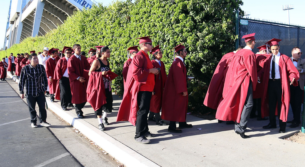 . Graduate candidates line up for a security check before checking in before Downey High School\'s 111th Commencement Ceremony Wednesday evening in Falcon Stadium at Cerritos College in Norwalk, CA Wednesday, June 18, 2014. (Photo by Mark Dustin for the Press-Telegram)