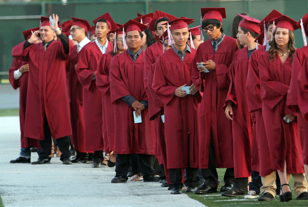 . Graduate candidates patiently wait in line during the Diploma Presentation during Downey High School\'s 111th Commencement Ceremony Wednesday evening in Falcon Stadium at Cerritos College in Norwalk, CA Wednesday, June 18, 2014. (Photo by Mark Dustin for the Press-Telegram)