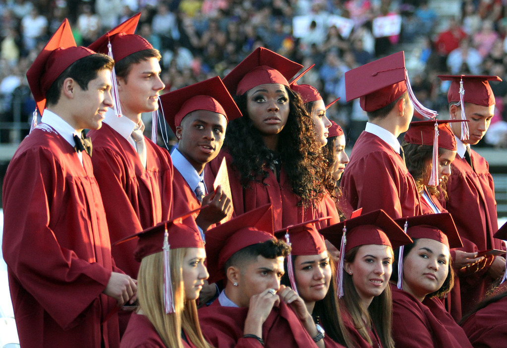 . Graduate candidates look for family and friends in the stands during Downey High School\'s 111th Commencement Ceremony Wednesday evening in Falcon Stadium at Cerritos College in Norwalk, CA Wednesday, June 18, 2014. (Photo by Mark Dustin for the Press-Telegram)