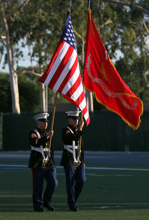 . Marine Color Guard carries the United States and Marine Corps flags for display during Downey High School\'s 111th Commencement Ceremony Wednesday evening in Falcon Stadium at Cerritos College in Norwalk, CA Wednesday, June 18, 2014. (Photo by Mark Dustin for the Press-Telegram)