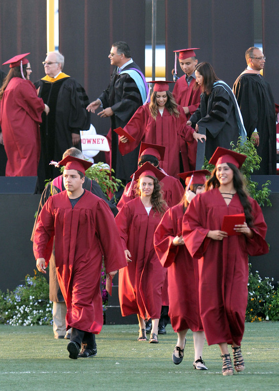 . Graduate candidates walk down the center aisle to their seats after receiving their diploma holders during Downey High School\'s 111th Commencement Ceremony Wednesday evening in Falcon Stadium at Cerritos College in Norwalk, CA Wednesday, June 18, 2014. (Photo by Mark Dustin for the Press-Telegram)