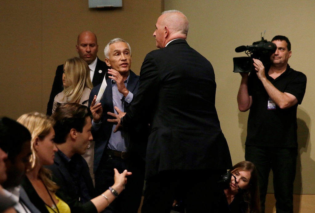 . A security guard for Republican presidential candidate Donald Trump removes Miami-based Univision anchor Jorge Ramos from a news conference, Tuesday, Aug. 25, 2015, in Dubuque, Iowa. Ramos stood up and began to ask Trump about his immigration proposal. (AP Photo/Charlie Neibergall)