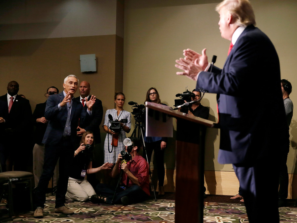 . Miami-based Univision anchor Jorge Ramos, left, asks Republican presidential candidate Donald Trump a question about his immigration proposal during a news conference, Tuesday, Aug. 25, 2015, in Dubuque, Iowa. Ramos was later taken from the room. (AP Photo/Charlie Neibergall)