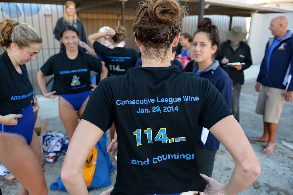. The Agoura girls water polo team puts on t-shirts given to them as a gift by their coach Jason Rosenthal after beating Newbury Park and breaking the Southern Section record for most consecutive league victories at 114, Wednesday, January 29, 2014, at Newbury Park. (Photo by Michael Owen Baker/L.A. Daily News)